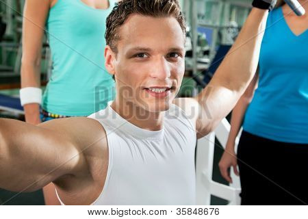 Fitness. Yung man at the gym doing arms exercises on a machine