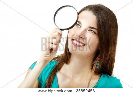 Beautiful teen girl looking through a magnifying glass over white background