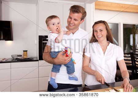 Mother preparing food with father and son standing beside smiling