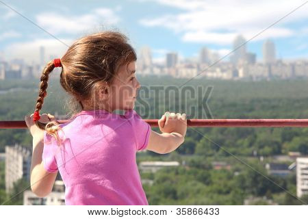 Little girl stand of roof of high building, back