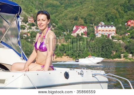 Young woman sunbathing on cutter on river