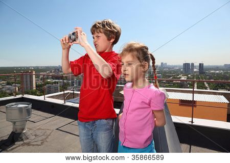 Sister, brother with camera photo city on roof of high building