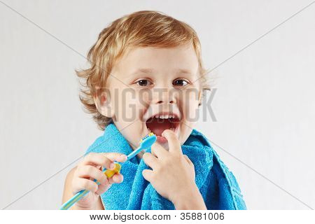 Little cute boy with toothbrush with pink toothpaste