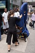 NEW YORK-JUL 28: Emily Hopkins transports her harp along 34th St to Penn Station on July 28, 2012 in