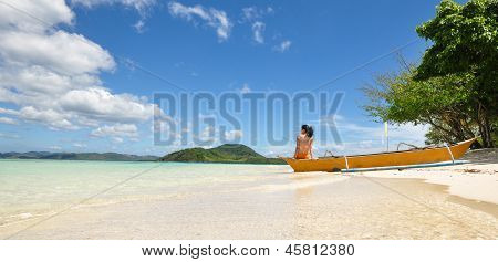 young girl sit on boat on white beach