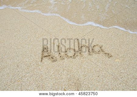 Inscription Aloha On The Sand At The Beach.