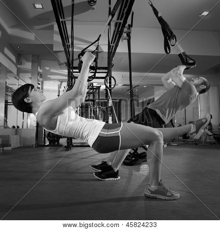 Fitness TRX training exercises at gym woman and man push-up workout