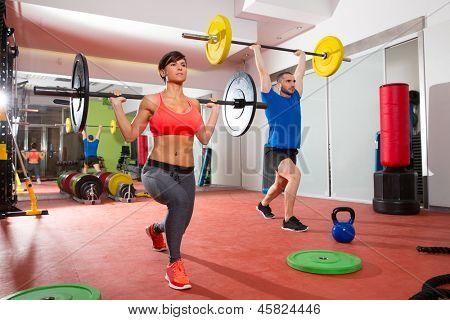 fitness gym weight lifting bar by woman and man group workout