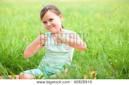 Little girl is showing thumb up gesture while sitting on green grass