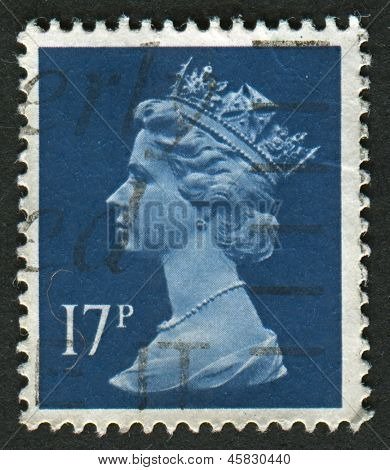 UK-CIRCA 1990:A stamp printed in UK shows image of Elizabeth II is the constitutional monarch of 16 sovereign states known as the Commonwealth realms, in Deep Blue, circa 1990.