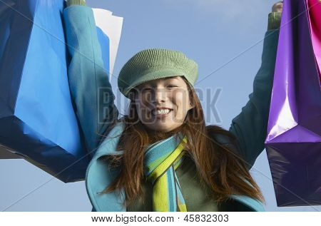 Young woman lifting up shopping bags