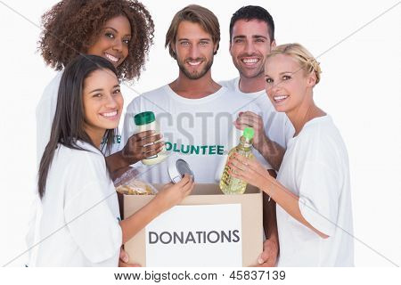 Happy volunteers putting food in donation box on white background