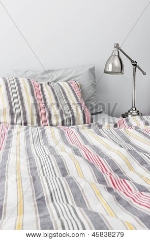 Metal Lamp Near Bed With Colorful Bedclothes