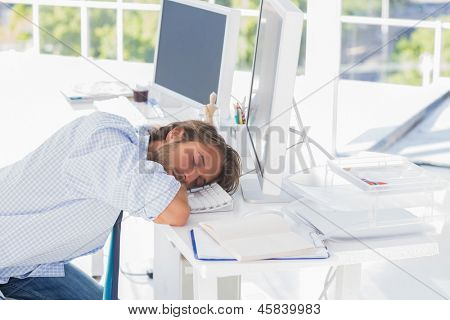 Man asleep at his desk in modern office