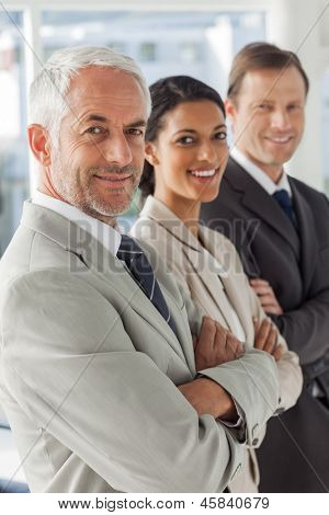 Cheerful business people looking in the same way with their arms crossed