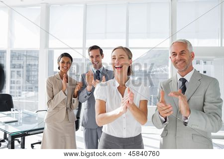 Group of business people applauding together in the meeting room