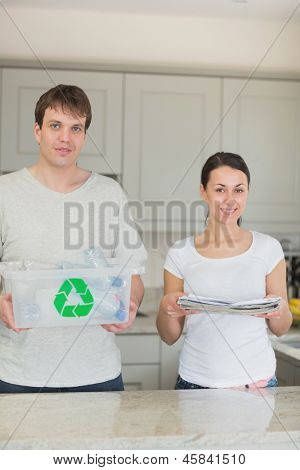 Smiling couple holding newspapers and recycling bin in kitchen