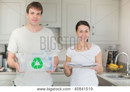 Couple holding recycling bin and newspapers in kitchen