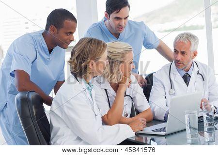 Smiling medical team using laptop to work
