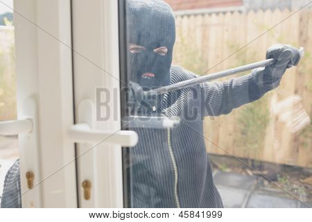 Burglar in garden opening the door with a crowbar