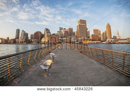 San Francisco cityscape with Ferry Terminal at sunrise from Pier 14 with metal swivel chairs, distorted fish eye perspective from Pier 14