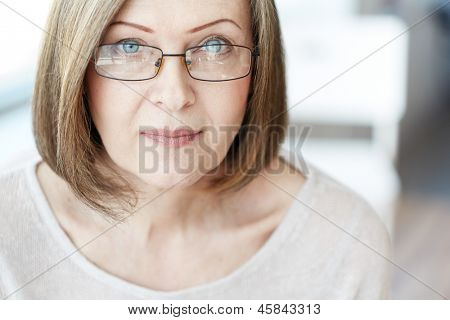 Mature woman in eyeglasses looking at camera