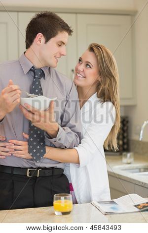 Man eats cereal while parter is embracing him in kitchen