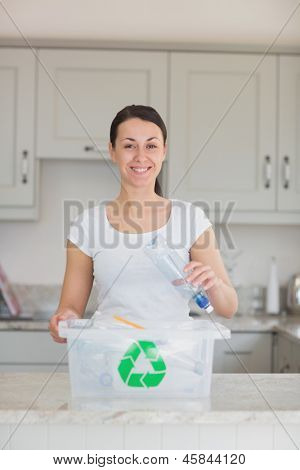 Smiling woman throwing bottle into recycling bin in kitchen