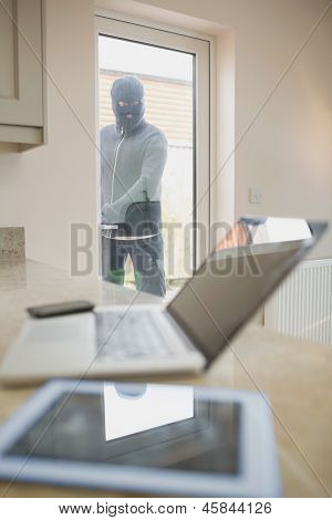 Burglar opening kitchen door and looking at laptop on counter of kitchen