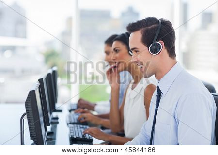 Smiling agent working in a call centre next to his colleagues