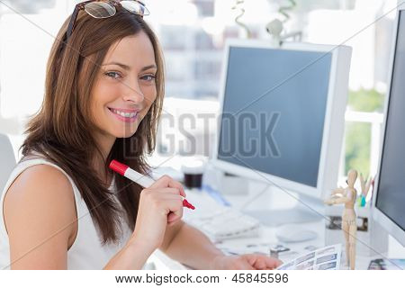 Photo editor about to make some cuts in the office at her desk