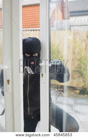 Burglar opening carefully the door with cro bar