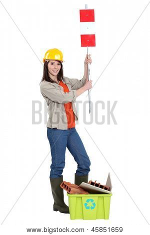 Tradeswoman holding up a traffic sign behind a recycling bin