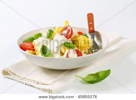 bowl of pasta salad with dressing on top