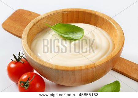 wooden bowl of creamy mayonnaise with basil and tomatoes
