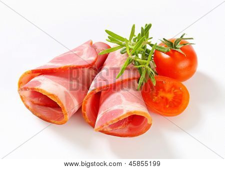 two rolled slices of smoked ham with cherry tomatoes and thyme