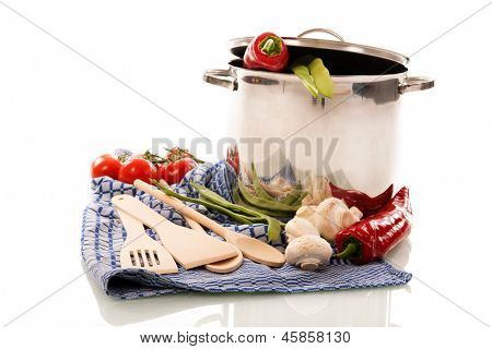 cooking with pan, wooden spoons, cloth and vegetables isolated over white background