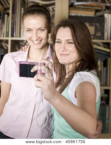 stock photo happy young girls making funny face while taking pictures of themselves through cellphon