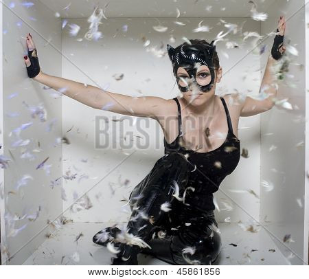portrait of beauty young woman in mask like cat in white box, feather in air