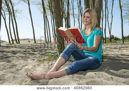 Beautiful blonde woman, reading a book on the sand of a beach, leaning against a tree, with her bare feet outstretched in the sand