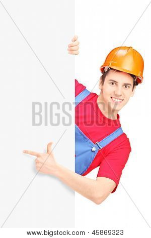Young construction worker with helmet gesturing on a blank panel isolated on white background