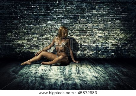 Nifty lady in underclothes with perfect figure by brick wall