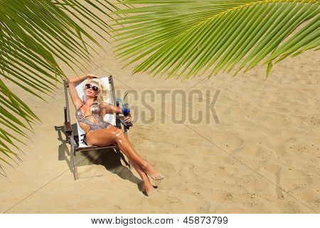 Beautiful young woman at the summer lounge under palm trees
