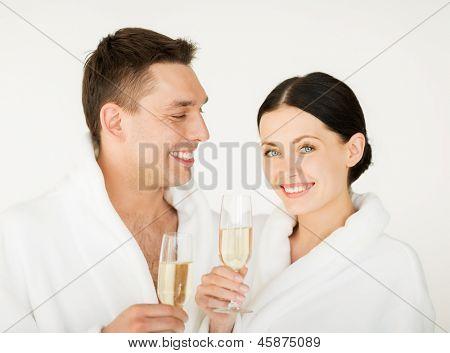 Bild des Paares in Spa-Salon in weißen Bademänteln mit Champagner