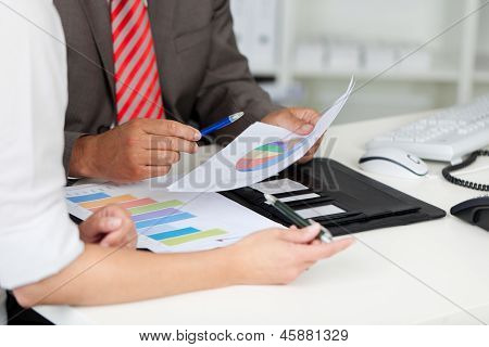 Businesspeople With Graphs At Office Desk