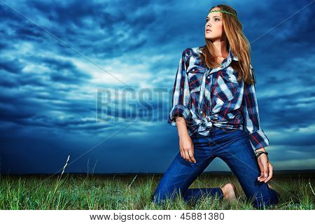 Romantic young woman in casual clothes standing in the field on a background of the storm sky.