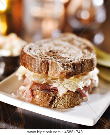 reuben sandwich with kosher dill pickle and coleslaw close up