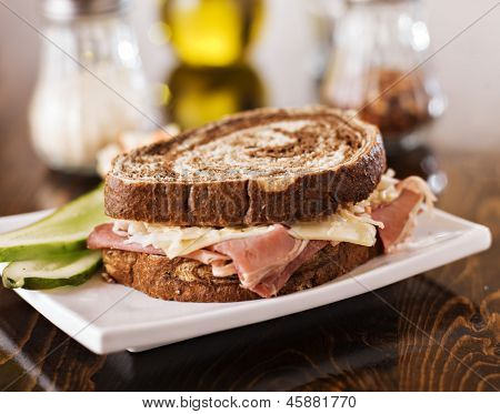 Reuben sandwich with kosher dill pickle and coleslaw on plate