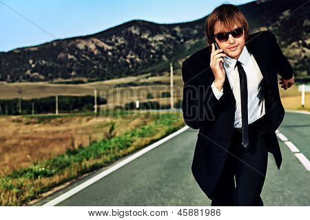 Businessman is running on the highway and talking on a mobile phone. Business struggle concept.