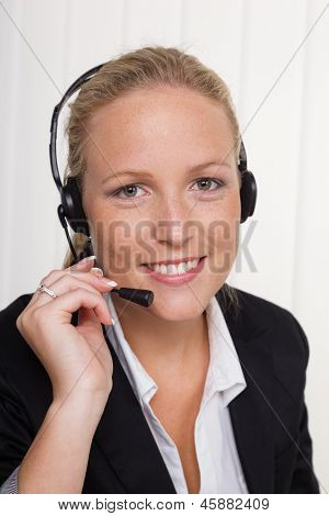 a friendly young woman with telephone headset in customer service with a customer. friendly sales associate.